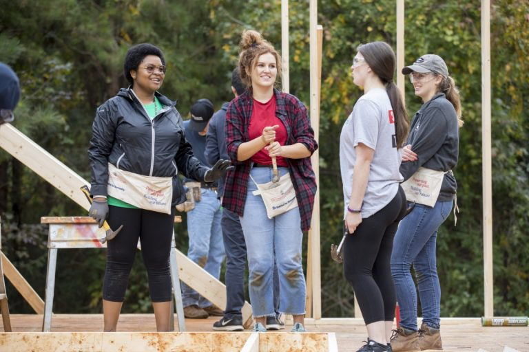 Students in Habitat for Humanity talking on a build site