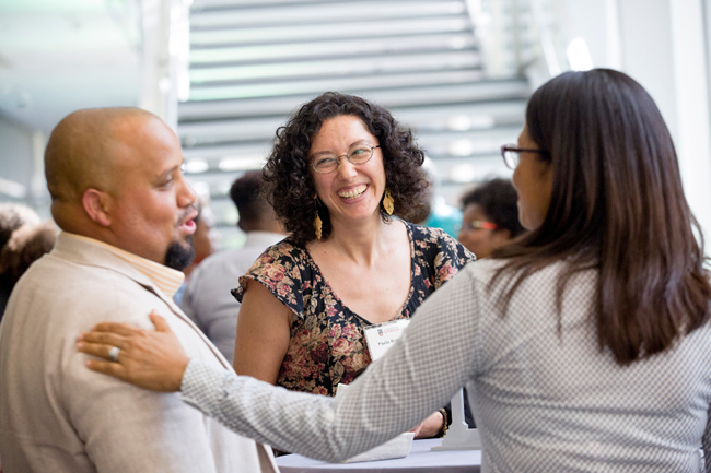 Three faculty members are facing each other, smiling and talking.