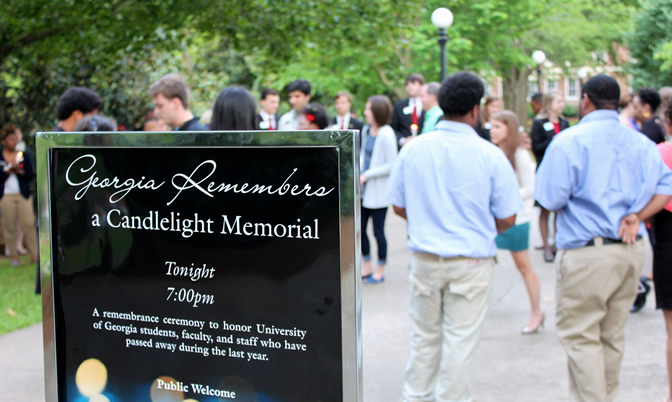 Two men in blue shirts and khaki pants are standing in front of the Georgia Remembers: A Candlelight Memorial sign