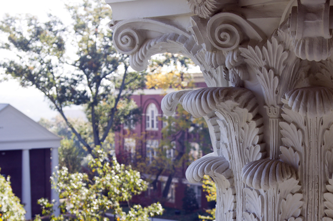 A close up of the top half of a detailed column. It is overlooking a small view of campus buildings and trees.