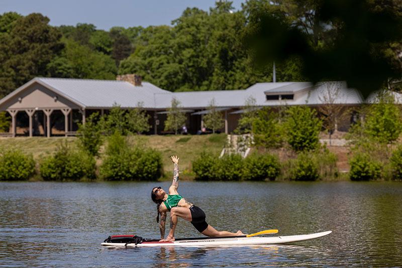 A student doing yoga on a paddleboard at Lake Herrick.